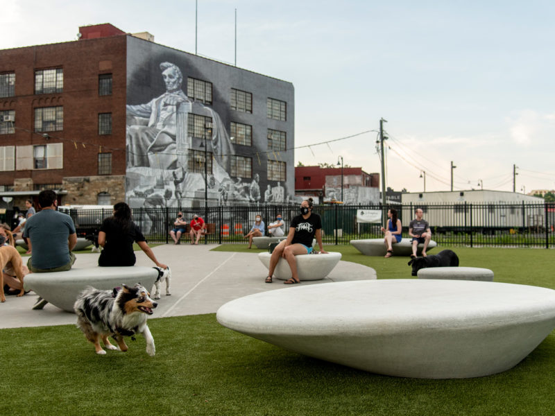 NoMa green park with dog park and people sitting onto Durbanis Supercell benches