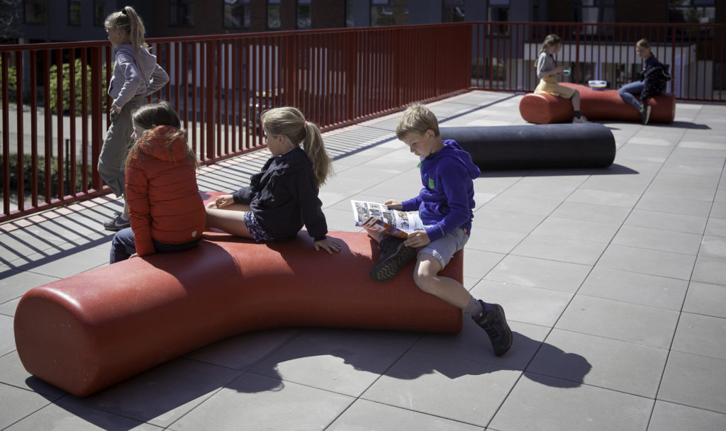 Boys and girls studying onto Durbanis benches. The outdoor design firm that manufactures its furniture in recycled plastic.