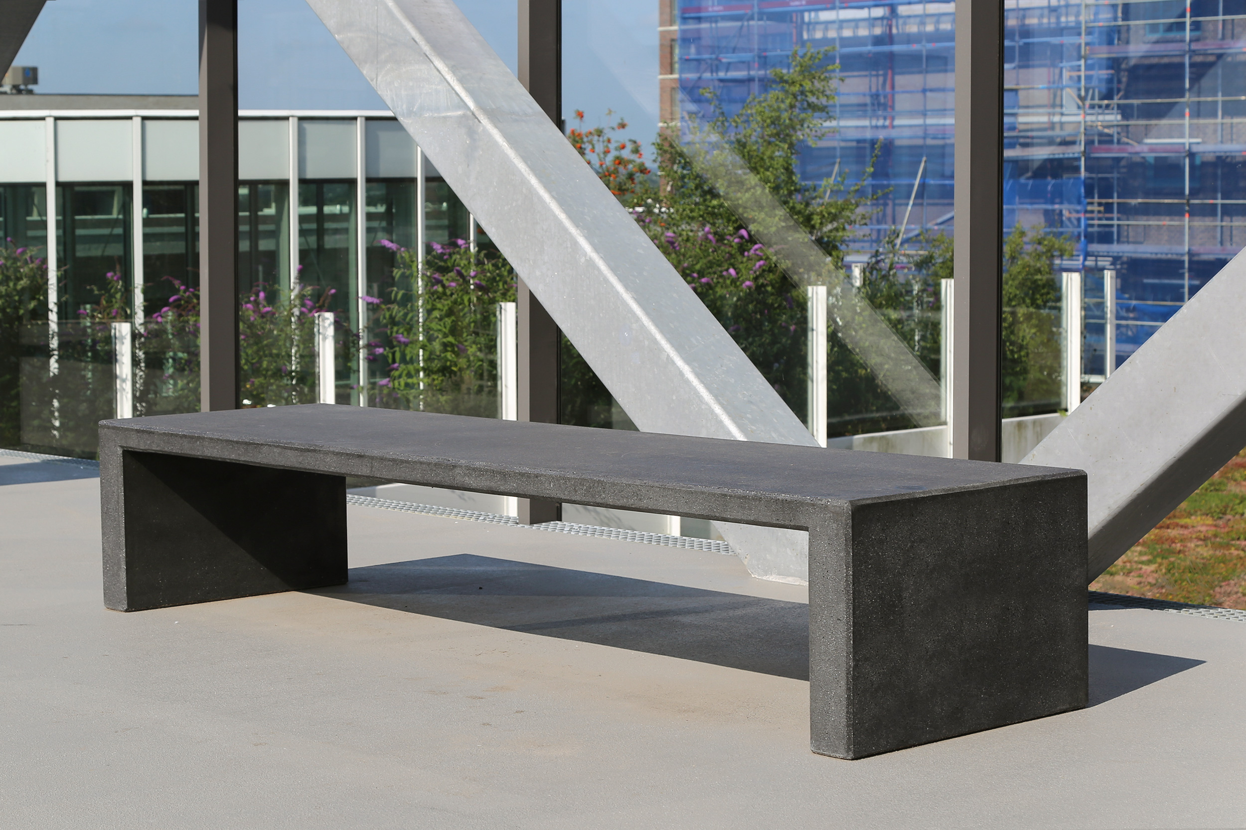 Public bench in black concrete at the Haasje Over in Eindhoven.